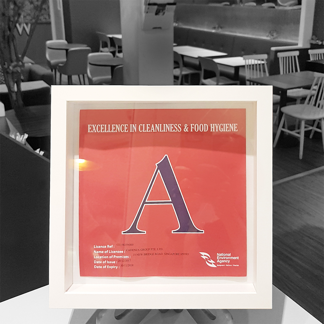 "A red Grade ""A"" Cerfificate in a white picture frame from the National Environment Agency for Excellence in Cleanliness and Food Hygiene. WANNA CUPPA is proud to keep this top hygiene rating since its very first inspecting."