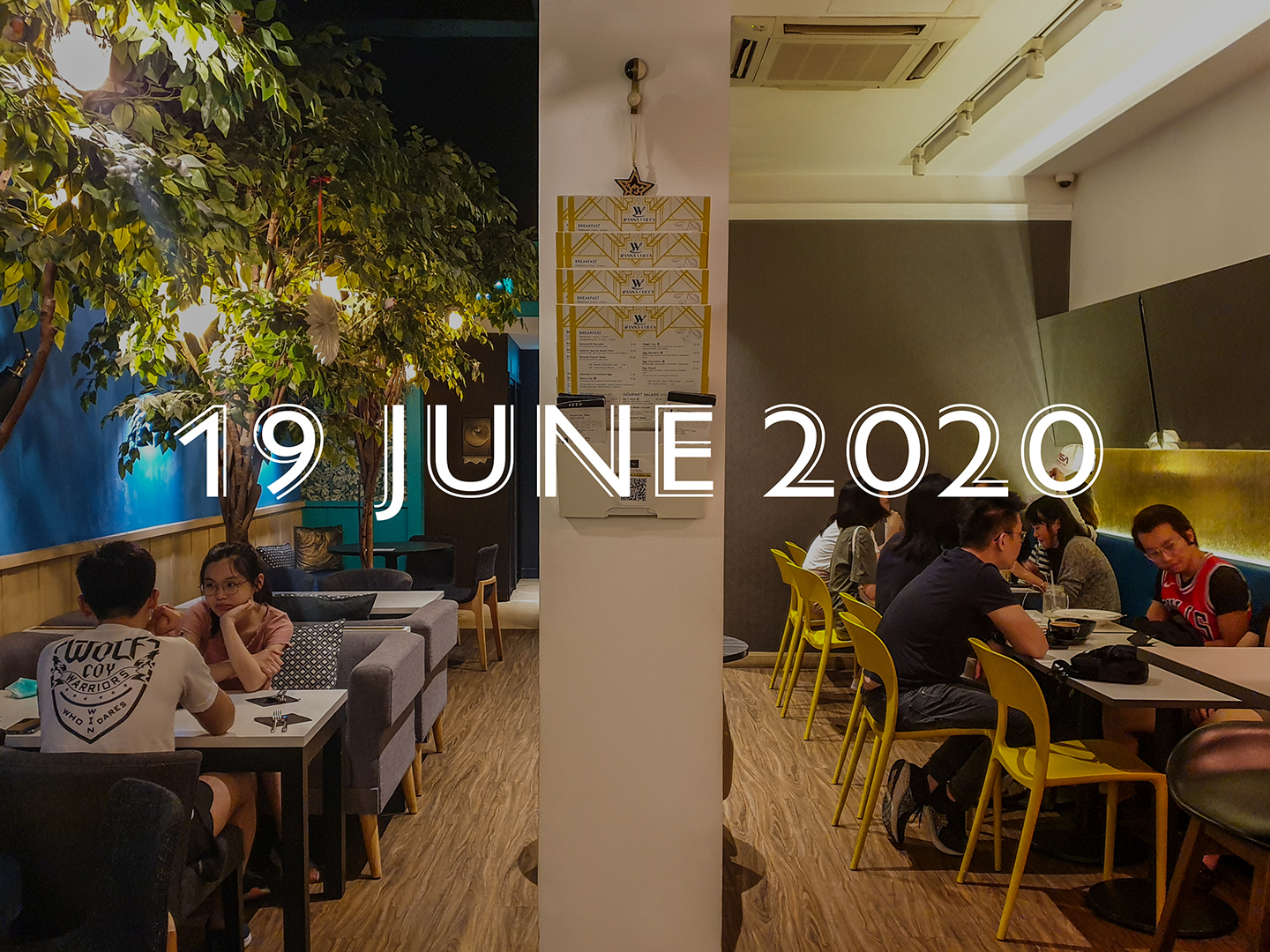 """An image of the rear dining area with dine-in customers to either side of a central column. To the left of image, there are three large trees amongst a variety of seating arrangements.. Seating area to the right has an inclined mirror over a blue banquette seating. """"19 June 2020"""" in white is centrally positioned within the image. It is the date when F&B businesses are allowed to have dine-in customers again if social distancing measures are implemented."""