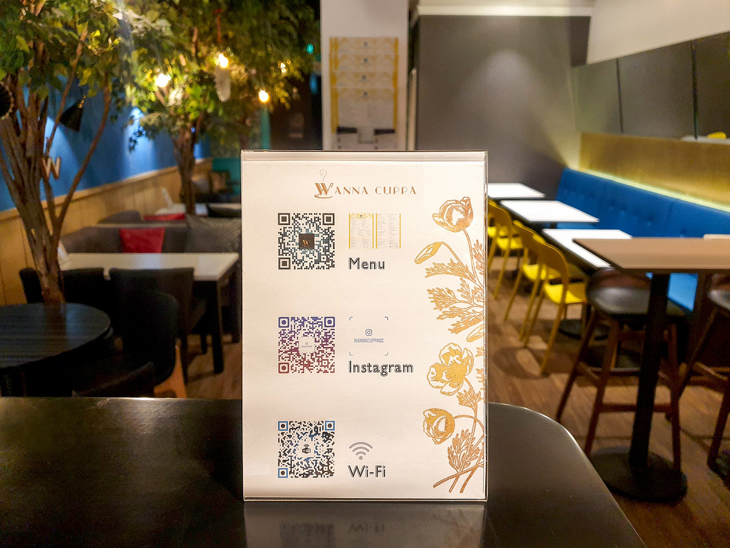 The backdrop is the rear dining area of the cafe featuring 3 large trees, an inclined mirror above blue banqette seating and a variety of seating arrangements. An transparent A5 display of QR codes is positioned centrally in the foreground. The QR Codes are for dine-in customers to scan for viewing the menu, connecting to the wi-fi and visiting WANNA CUPPA's Instagram account. The A5 display has a white background with gold flowers to one side. It sits on top of a black countertop.